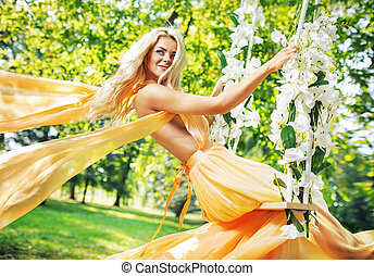 Pretty blond lady sitting on the ornate seesaw