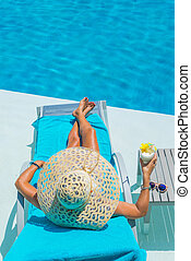 Pretty blond woman a cocktail in a swimming pool