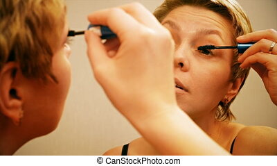 Pretty blond woman applying mascara make-up