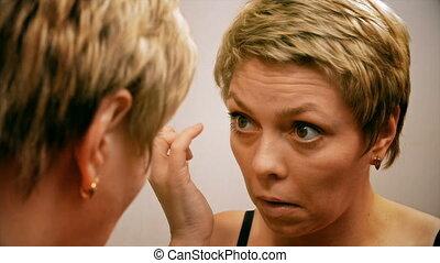 Pretty blond woman applying mascara make-up on her eyelashes...