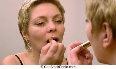 Pretty blond woman applying red lipstick makeup