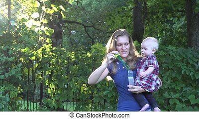 Pretty blond woman blowing soap bubbles and beautiful baby child enjoy it in bright sun light. 4K