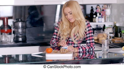 Pretty Blond Woman Eating a Bread at the Kitchen