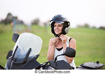 Pretty blond woman enjoying a motorbike ride in countryside....
