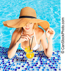 Pretty blond woman enjoying cocktail in a swimming pool
