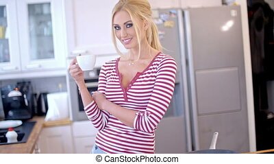 Pretty blond woman enjoying her morning coffee