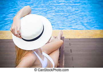 Pretty blond woman in a hat by a swimming pool