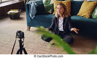 Pretty blond woman is talking and looking at camera recording video for her online blog sitting on floor in modern flat. Technology, mass media and people concept.