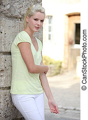 pretty blond woman standing in front of her house
