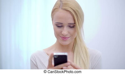 Pretty blond woman texting on her mobile