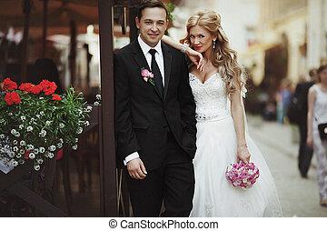 Pretty blonde bride leans on groom's shoulder standing behind a street cafe