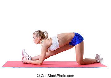 Pretty blonde doing aerobics exercises on mat