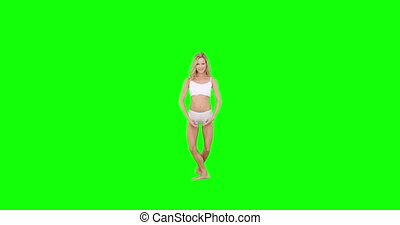 Pretty blonde doing ballet dancing on green screen background