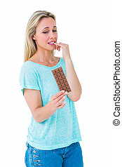 Pretty blonde feeling guilty to eat bar of chocolate