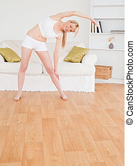 Pretty blonde female stretching in the living room