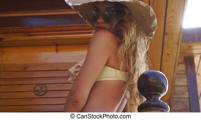 pretty blonde girl in sunglasses and straw hat looking at the camera summer time