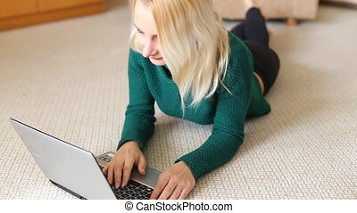 Pretty blonde girl lying on carpet with laptop