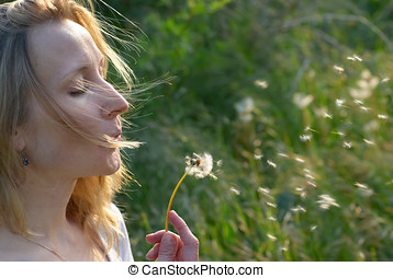 Pretty blonde girl with dandelion