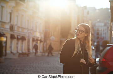 Pretty blonde girl with long hair wearing coat, posing in sun glare. Empty space