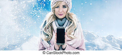 Pretty blonde holding a cellphone, winter bacgkround
