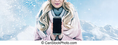 Pretty blonde holding a smartphone, winter weather
