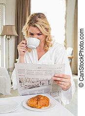 Pretty blonde in bathrobe drinking coffee and reading ...