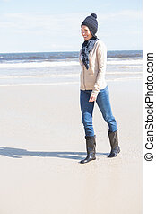 Pretty blonde in jeans walking on the beach