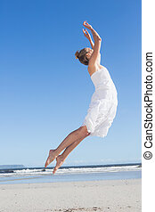 Pretty blonde in white dress leaping on the beach