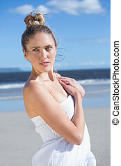 Pretty blonde in white dress posing on the beach