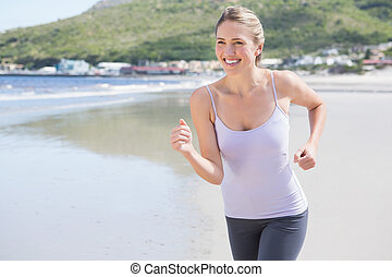 Pretty blonde jogging on the beach