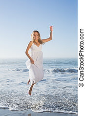 Pretty blonde jumping at the beach in white sundress