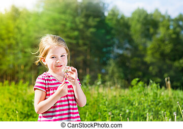Pretty blonde little girl with dandelion in sunlight