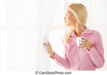 Pretty Blonde Looking Through A Window