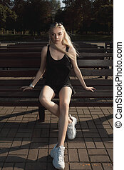 Pretty blonde model in stylish apparel posing on a bench in sunny day
