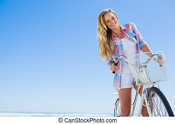 Pretty blonde on a bike ride at the beach smiling at camera ...
