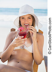Pretty blonde relaxing in deck chair on the beach with cocktail
