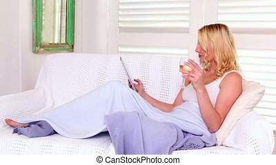 Pretty blonde relaxing on sofa with tablet pc - Pretty...