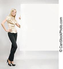 Pretty blonde secretary showing an empty board,lots of copyspace