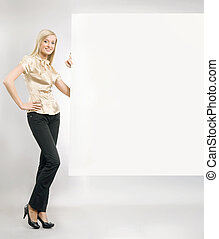 Pretty blonde secretary showing an empty board,lots of copyspace