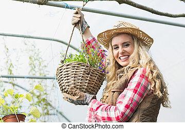Pretty blonde showing a hanging flower basket