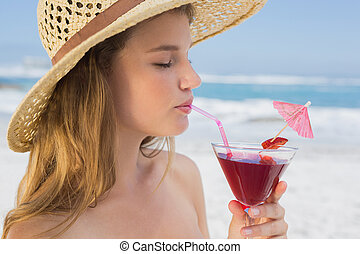 Pretty blonde sipping cocktail on the beach