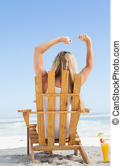 Pretty blonde sitting in deck chair with a cocktail