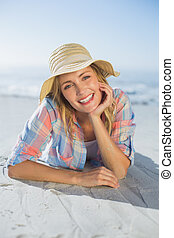 Pretty blonde smiling at camera at the beach lying on the sand on a sunny day