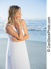 Pretty blonde standing at the beach in white sundress