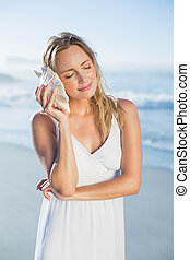 Pretty blonde standing at the beach in white sundress listening