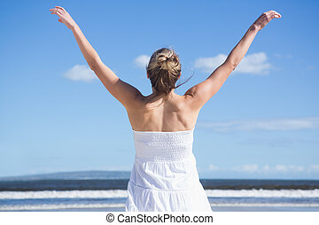 Pretty blonde standing with arms outstretched on the beach...