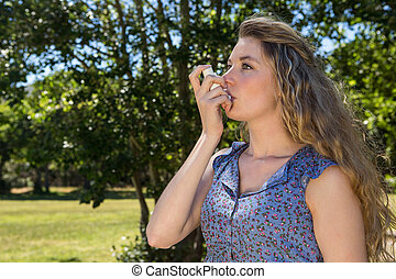 Pretty blonde using her inhaler