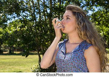 Pretty blonde using her inhaler