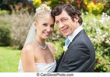 Pretty blonde wife hugging her new husband smiling at camera