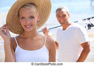 pretty blonde with sun hat and boyfriend in background